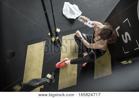 Delightful woman with curly hair sits on the floor in the gym next to black partition. She wears dark sportswear with red sneakers. Girl drinks water from the bottle. Shoot from the top view.