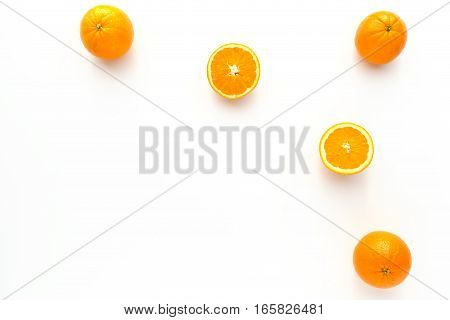 Closeup of whole and halved oranges on white as food background with lots of copy space.