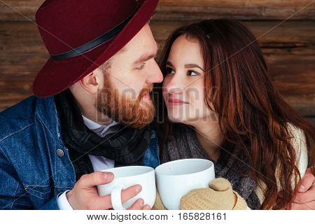 Happy couple drinking tea wood house winter portret