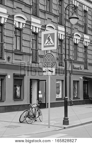 road signs and pedestrian crossings in city black and white