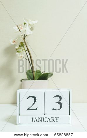 Closeup white wooden calendar with black 23 january word with white orchid flower on white wood desk and cream color wallpaper in room textured background selective focus at the calendar