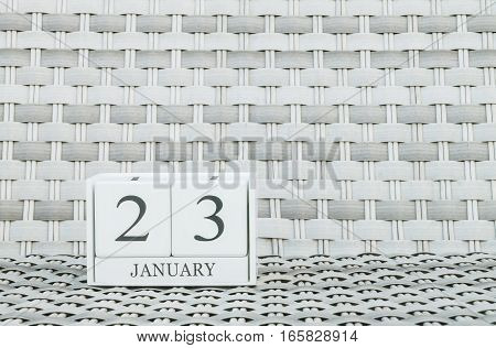 Closeup surface white wooden calendar with black 23 january word on blurred weave wood chair textured background with copy space selective focus at the calendar