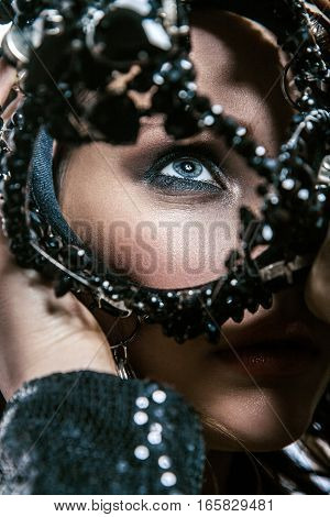 Fashion beauty portrait of young beautiful young woman with makeup, blue eyes and freckles on her face holding black crown in front of her face.