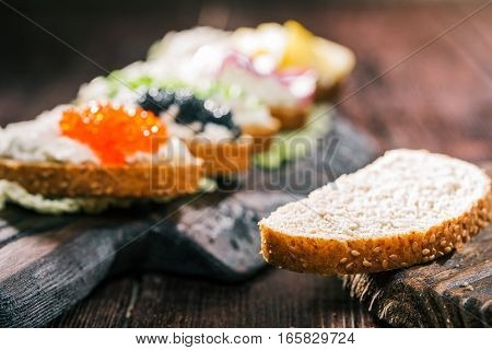 Bran toast and sandwiches with various tops on the background
