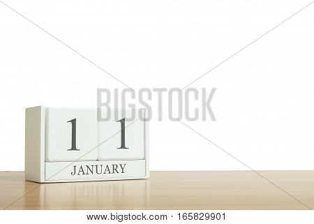 Closeup surface white wooden calendar with black 11 january word on blurred brown wood desk isolated on white background with copy space selective focus at the calendar