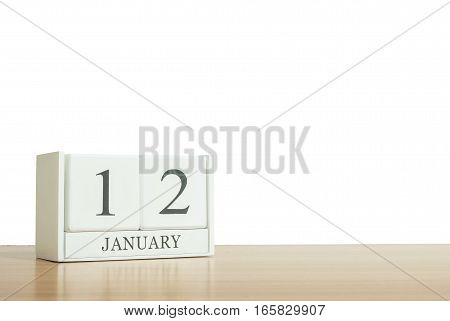 Closeup surface white wooden calendar with black 12 january word on blurred brown wood desk isolated on white background with copy space selective focus at the calendar