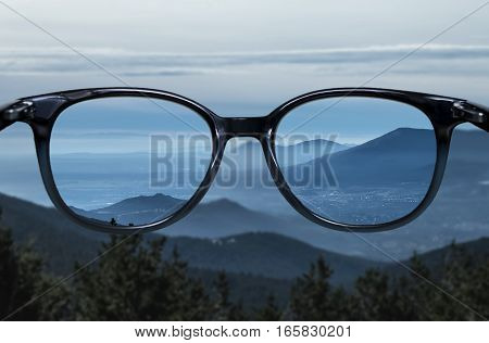 Clear vision through glasses over blue mountain landscape