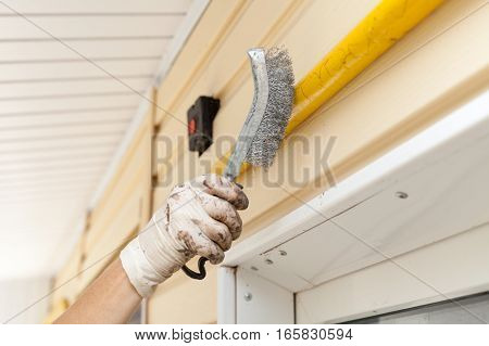 Removal of old coats of paint from the metal gas pipe using metal brush. Clean the surface with a brush. Repair work painting.