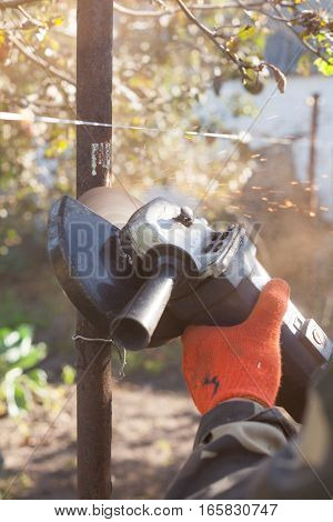 Worker in gloves cleans rust on the old metal pipe with a grinders machine.