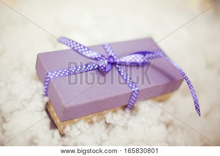 purple gift boxes with satin ribbons on the snow. Christmas gifts near Christmas tree
