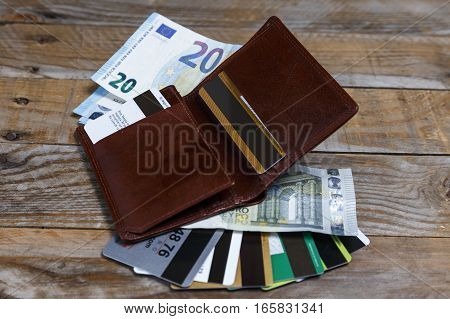 Banknotes, euro coins and credit cards in a leather wallet on an old wood