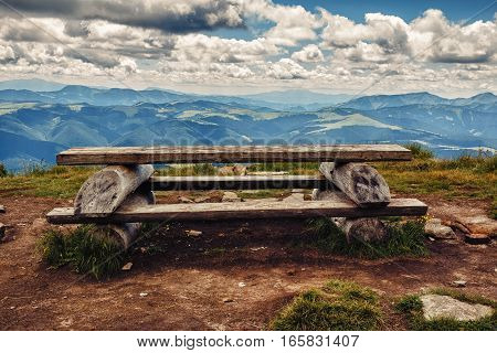 Wooden table and bench for relaxation on the top of Pip Ivan mountain nature landscape in Carpathians Ukraine. View to Romanian mountain.