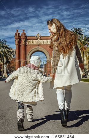 Modern Mother And Daughter In Barcelona, Spain Walking