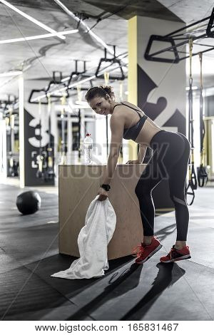 Gorgeous smiling woman with a white towel in the left hand leans on the wooden box in the gym. She wears dark top and pants, red sneakers. Her right hand is on the box, legs are on the toes.