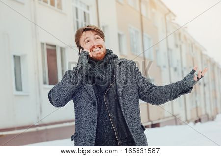 stylish man with a cell phone on the background of the house