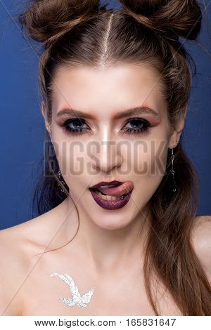 Portrait Of A Brutal Girl On A Blue Background.