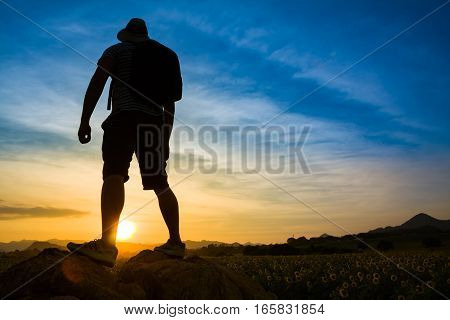 Silhouette of successful traveler look at the sunset