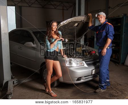 Beautiful Girl And Auto Mechanic Standing Near The Car