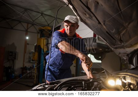 Car Mechanic Working In Auto Repair Service. Repairing Car Using
