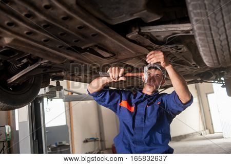 Portrait Of Car Mechanic Working With Tools Under Car