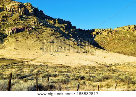 Barren and desolate rural landscape with grasslands, sagebrush, rocky hills, and a rustic wooden fence taken near Tehachapi, CA during sunset