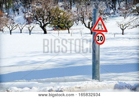 danger road sign snow winter path country road