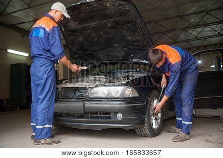 Examining Car At The Auto Repair Shop