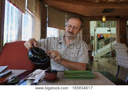 A middle-aged man in a cafe at a table, pours himself tea