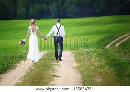Back view of romantic couple of bride and groom walking hand in hand on rural road