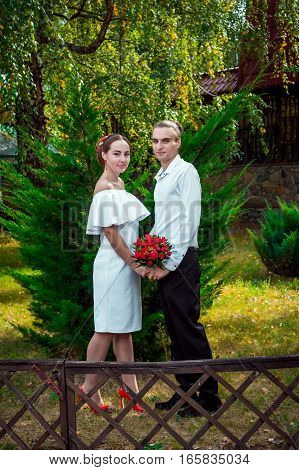 Happy loving wedding couple posing in the autumn park. Young handsome smiling  groom holding hands of at his beautiful bride in white dress with bouquet of red roses.