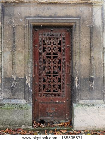 Brown rectangle and ornate iron door, weathered and decaying