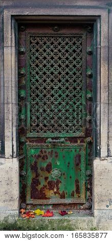 Rusty and shattered old green metal door. The iron is decaying and rusting. In the center is a repetitive pattern with small clover (quatrefoil) ornaments.