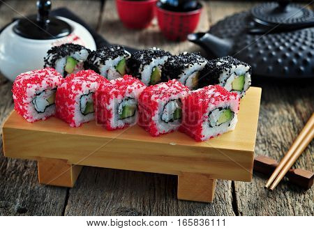 Homemade sushi with crab meat, avocado and flying fish caviar on a serving board.
