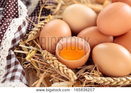 Farmers eggs in straw and tablecloth on wooden background.