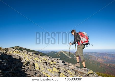 Man Backpacker Walking On The Rocky Ridge Of The Mountain