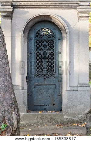 Blue closed steel door of a mausoleum at a cemetery with a round top frame. The ornate iron door itself has a cross and other ornaments.