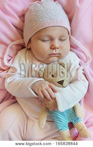 Cute newborn baby in hat sleeps on a pink blanket with a toy teddy bear