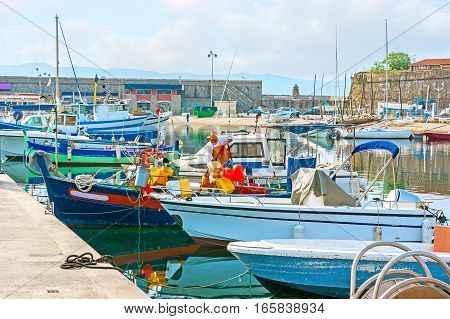 The colorful fishing boats in old port of Ajaccio with the ramparts of the Citadel on the background Corsica France.