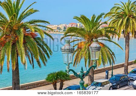 The scenic old fashion streetlight with the lush palms and blue waters of the sea and colorful houses of the central city promenade on the background Ajaccio Corsica France.