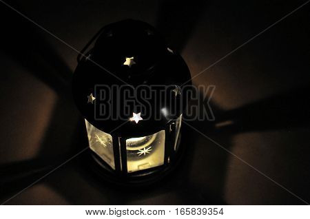 Candle lantern in dark with shades shining star in black background with soft fire