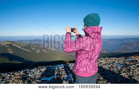Young Woman Hiker Taking Picture With Her Smartphone
