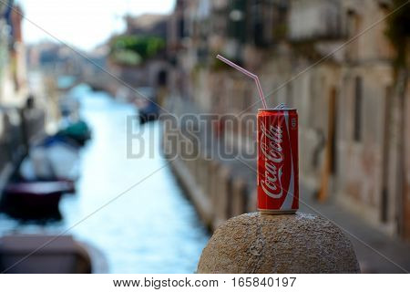 Venice Italy - September 9 2016: Coca Cola can with straw standing on top of stone bollard over canal in Venice Italy.