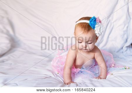 Newborn baby girl wearing a white crocheted crown, ballerina tutu, and ballet slippers. She is on pink rose ribbon fabric.