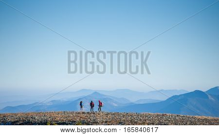 Group of three young athletic tourists enjoying the view on the rocky mountain plato on their backpacking trip. Beautiful mountains on background. Healthy lifestyle concept. Rear view. Copy space. Freedom.