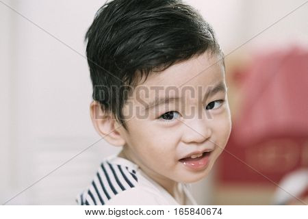 Portrait of cute Asian kid smiling and look happy.