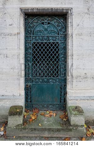 a door with a bat - closed, turqoise colored iron entry to an ancient crypt / tomb at a cemetery. Ornate with faces, grapes and in the round arch the nocturnal flying animal, spreading its wings.