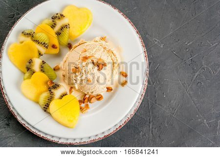 Romantic foods for Valentine's Day. Fruit salad with ice cream ball on a plate top view. Fruits cut in the shape of hearts