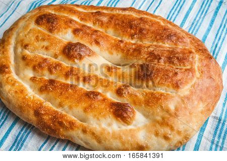 Armenian homemade wheat flat bread matnakash cools on a towel after baking