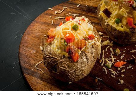 Homemade baked potato with cheese and vegetables copy space close view