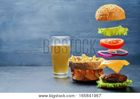 Flying burger with French fries and beer on a dark background.